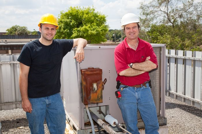 Image of two HVAC techs in front of an industrial compressor unit.