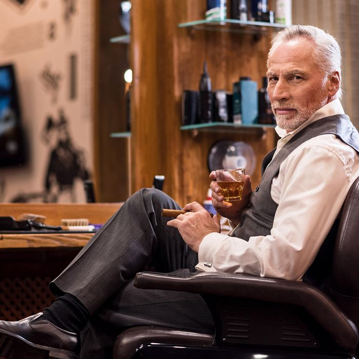 A man sits inside a barbershop.