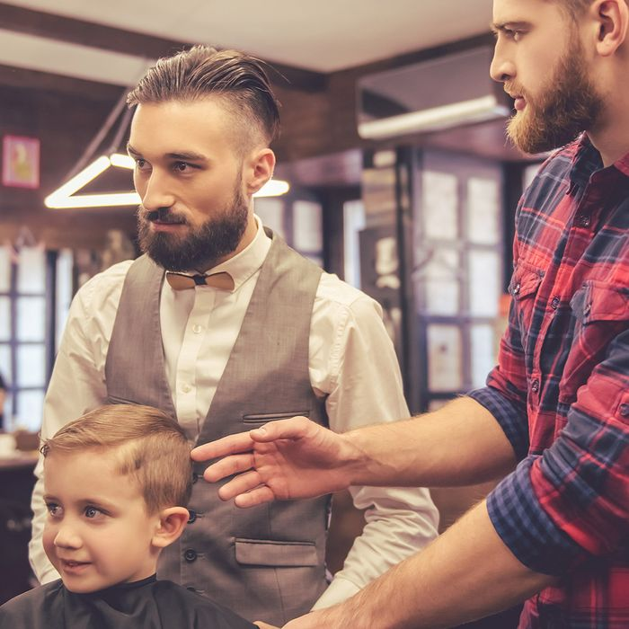 Two barbers in training cut a young child's hair.