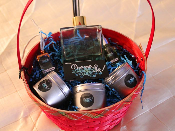 A red gift basket with three hawaiian-inspired candles and scented oils from Ohanale.