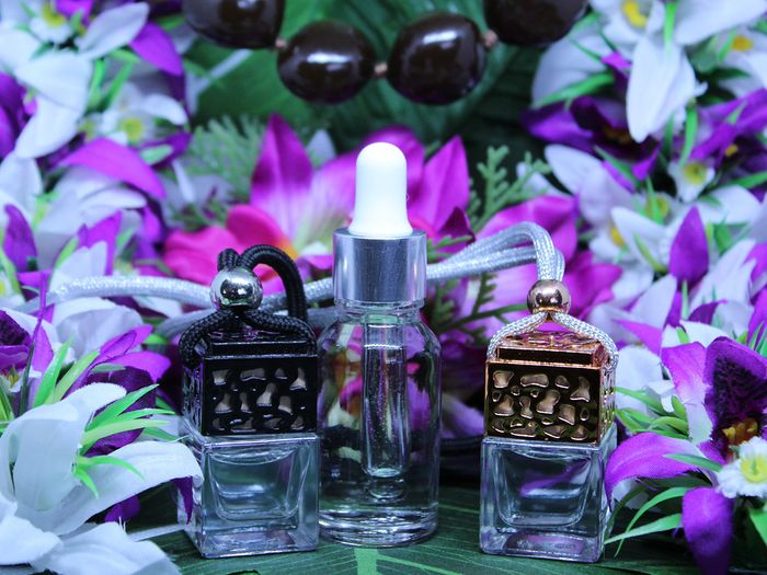 Three cases of scented, diffusible oils set before a gorgeous backdrop of purple and white Hawaiian flowers.