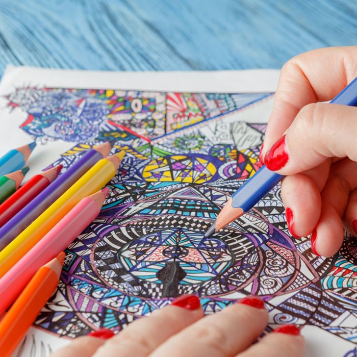 A hand holding a blue colored pencil coloring in an intricate pen drawing.
