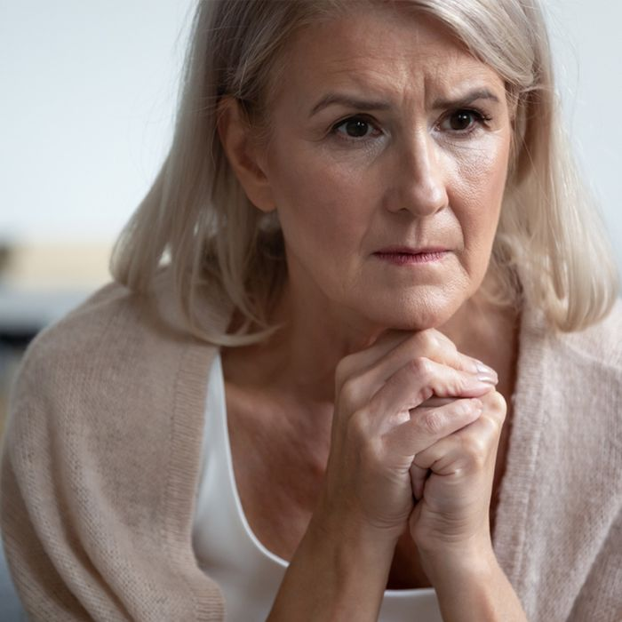 An older woman resting her chin on clasped hands, lost in thought.