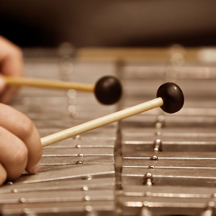 Two wood mallets hovering above a xylophone.