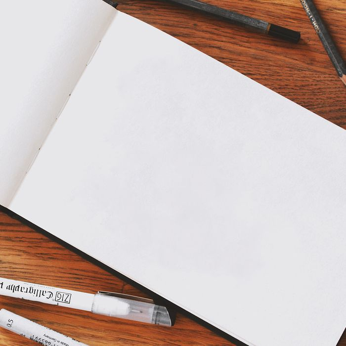 A blank page in a sketchbook surrounded by drawing pens and pencils.