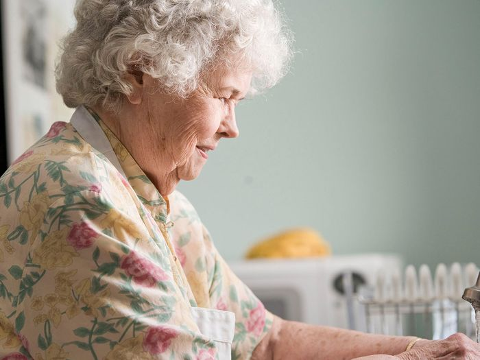 An older woman with grey hair standing in her kitchen clasping her hands out in front of herself.