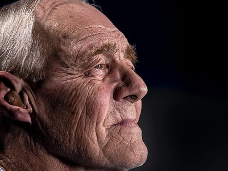 An upclose look at an older man's deep-set face, staring off into the distance.