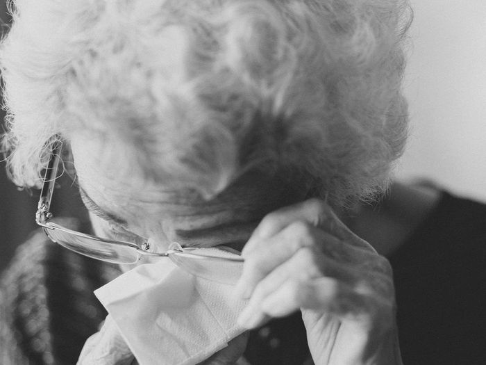 An older woman with white hair and glasses wiping her eyes with a tissue.
