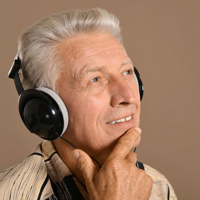 An elderly man with white hair wearing headphones, looking off into the distance with a finger resting on his chin.