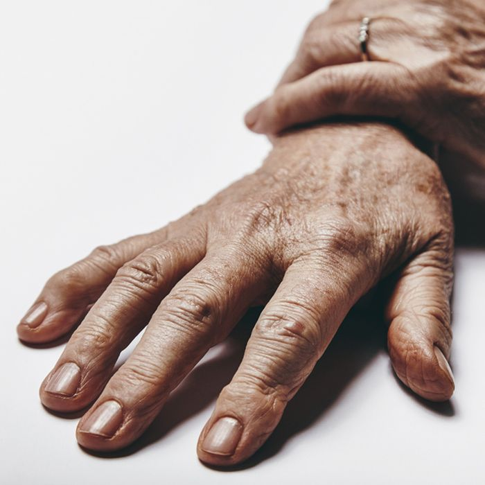 A pair of old woman hands on a grey surface.