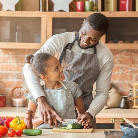 Father cooking in the kitchen with his daughter.