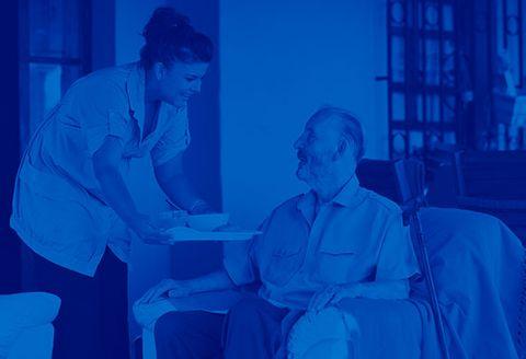 nurse serving meal to elderly man