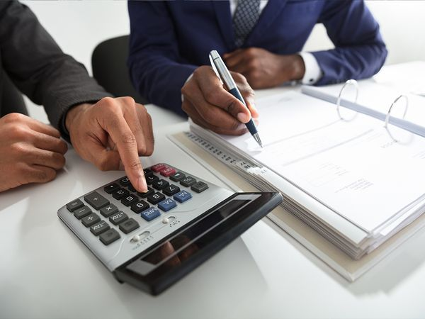 Financial paperwork, calculator, money, and credit cards on a table.