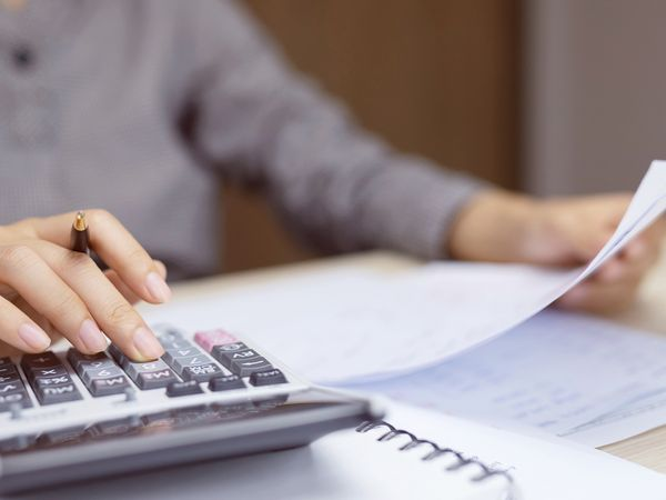 Woman looking at invoices and using a calculator.