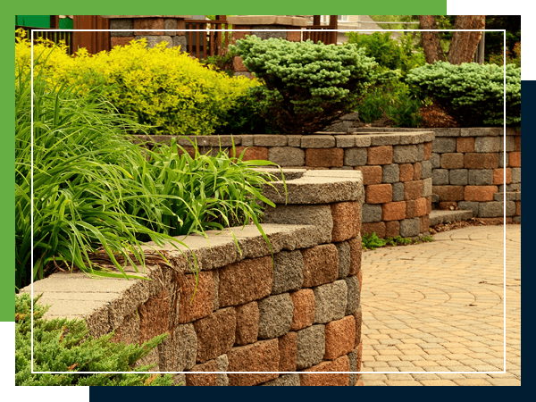 Image of brick plant holders with a variety of plants growing