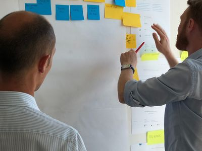 Two businessmen standing at a whiteboard planning out with sticky notes.