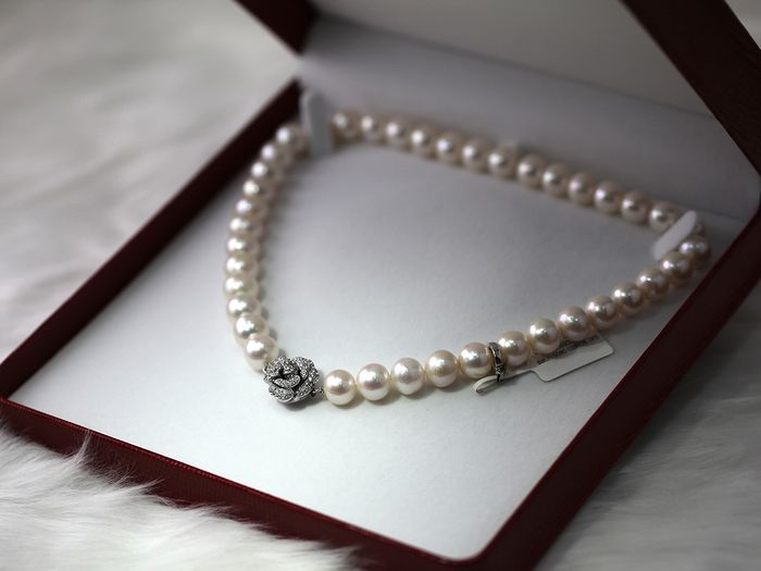 Image of a pearl necklace with diamond pendant in box
