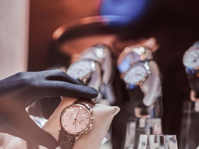 Close-up of the seller`s hand in gloves shows the exclusive men`s watch from the new collection in the luxury jewelry store