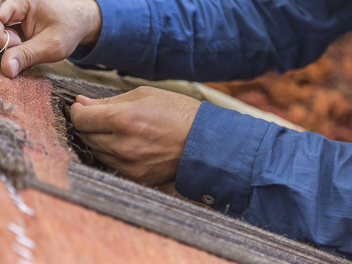 image of a man working on the threading of a large oriental rug