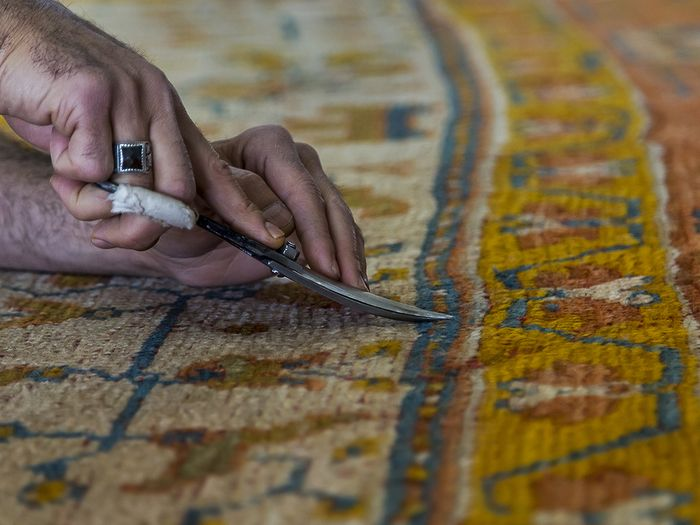 image of a man restoring an old oriental rug