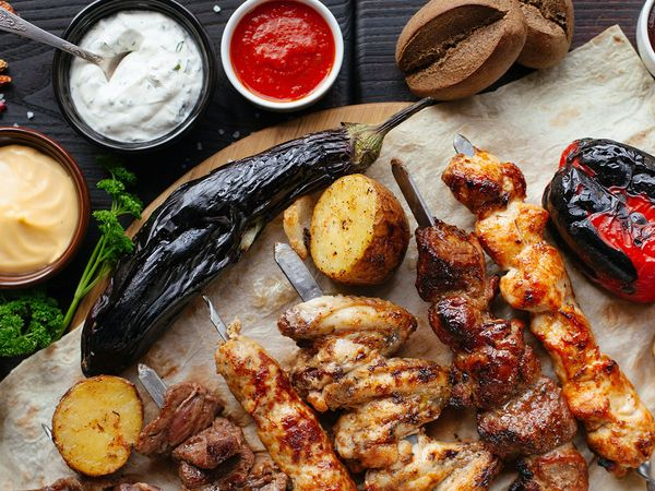 A plate of jerk chicken and other roasted meats and vegetables.