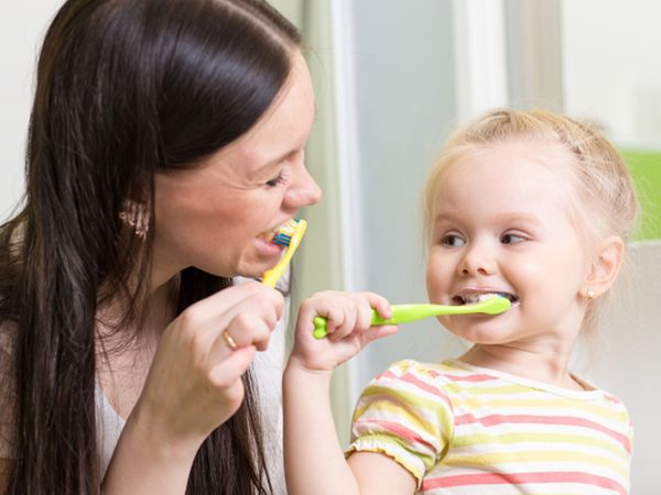 Parent and child brushing their teeth.