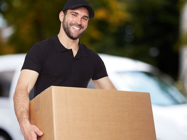 A male mover carrying a moving box