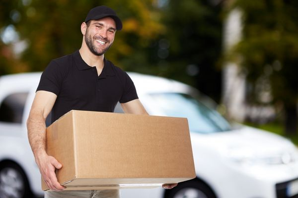 An image of a man in a black shirt and hat smiling and carrying a large moving box