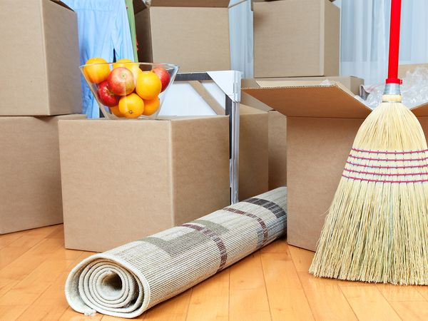 Several moving boxes stacked in a room with a rug, a broom, and a bowl of fruit