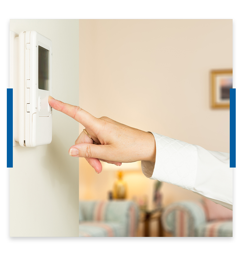 Woman's hand changing the temperature on the thermostat.