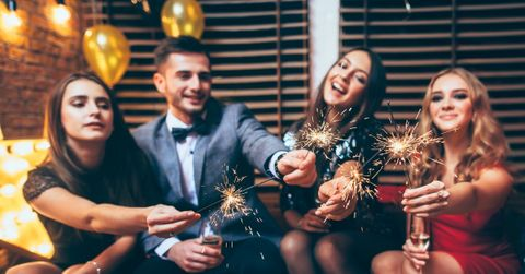 Image of a group of friends holding sparklers at a party