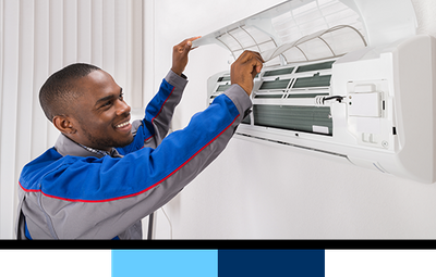 Technician repairing wall-mounted AC unit