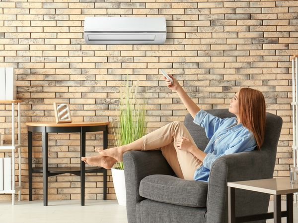 woman using a remote to turn on her mini-split air conditioner