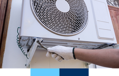 Close-up shot of an electrician with a wrench repairing an air conditioner.