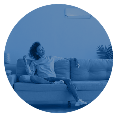 Woman relaxing and enjoying air conditioning from a small wall unit.