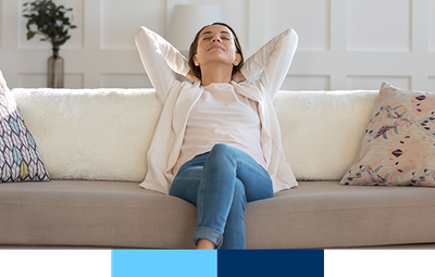 Happy woman leaning back on couch