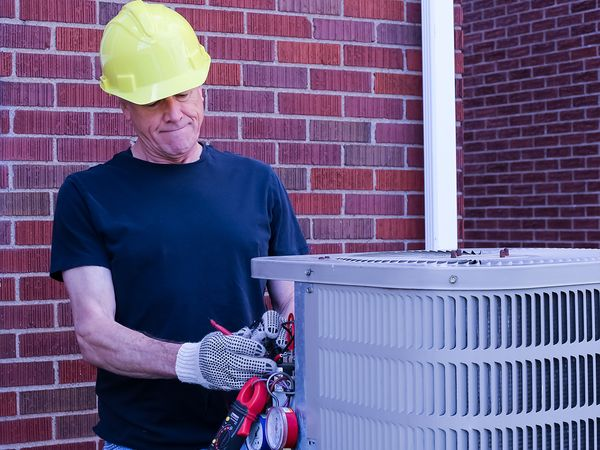 Heating and Cooling technician repairing AC unit