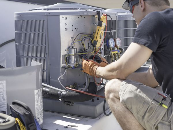 HVAC technician working on air conditioning unit