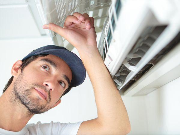 HVAC technicians installing a mini-split air conditioner