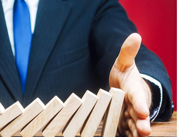 Businessman stopping wooden dominoes from falling with his hand