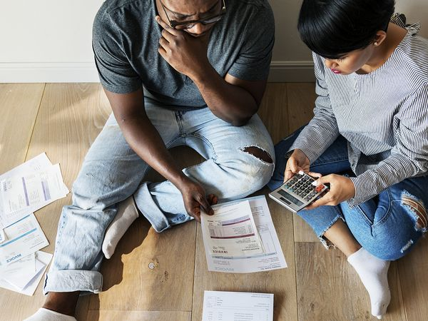 Stressed out man and woman sitting on the floor surrounded by billing statements