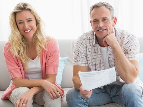 Happy woman and man sitting on a couch with billing statements and a calculator