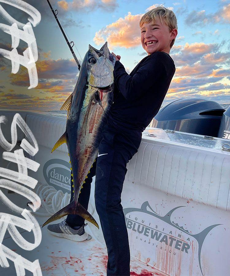 Kid holding big fish on boat