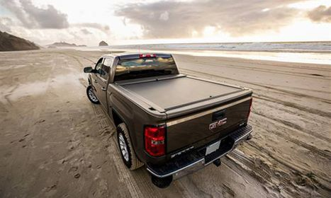 Truck on the beach with water behind it