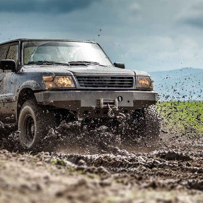 A pickup off-roading on a muddy road with mud flying