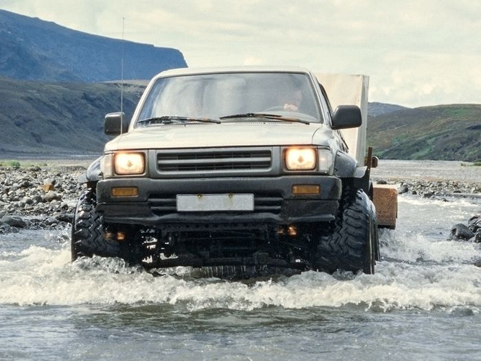 A pickup with aftermarket accessories fording a river