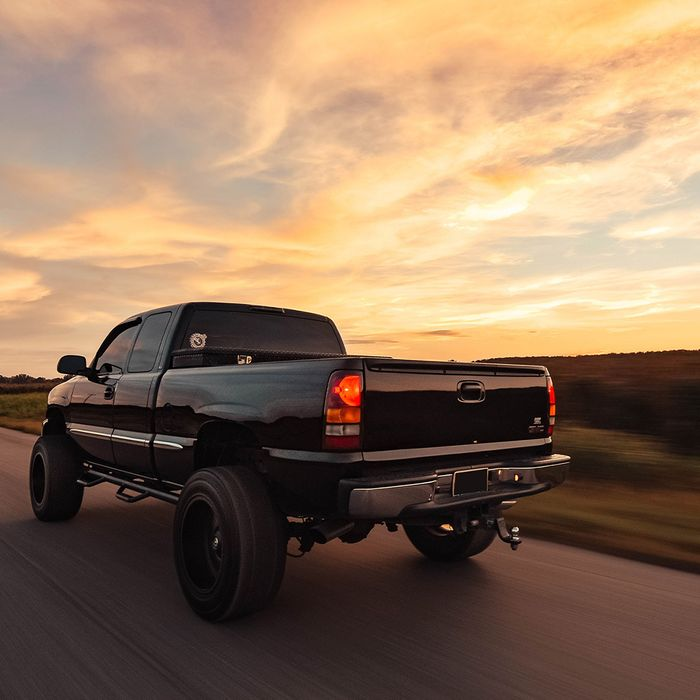 A black pickup truck driving into the sunset