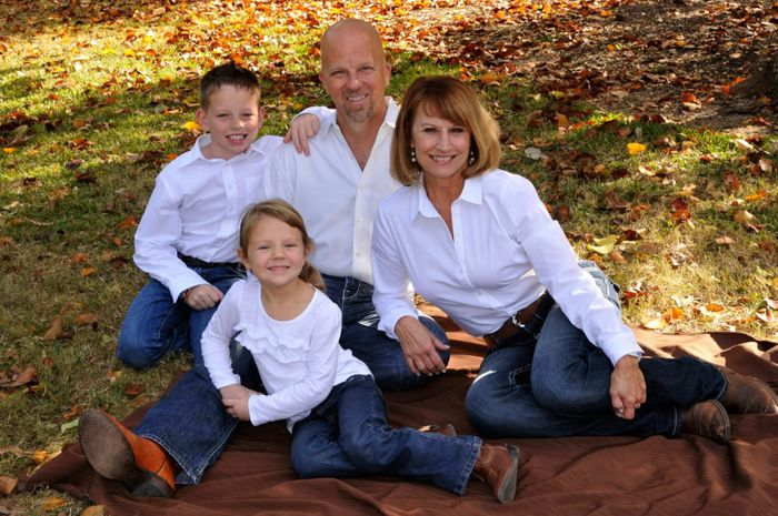 Family of four sitting on a blanket