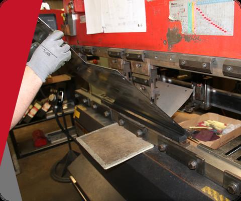 man feeding sheet metal into machine