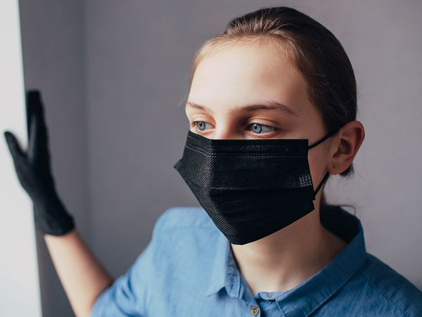 A woman wearing a black disposable face mask and black nitrile gloves